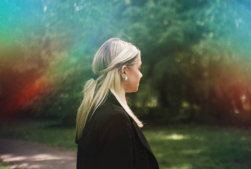 Frau im schwarzen Hemd, das auf Rasen steht