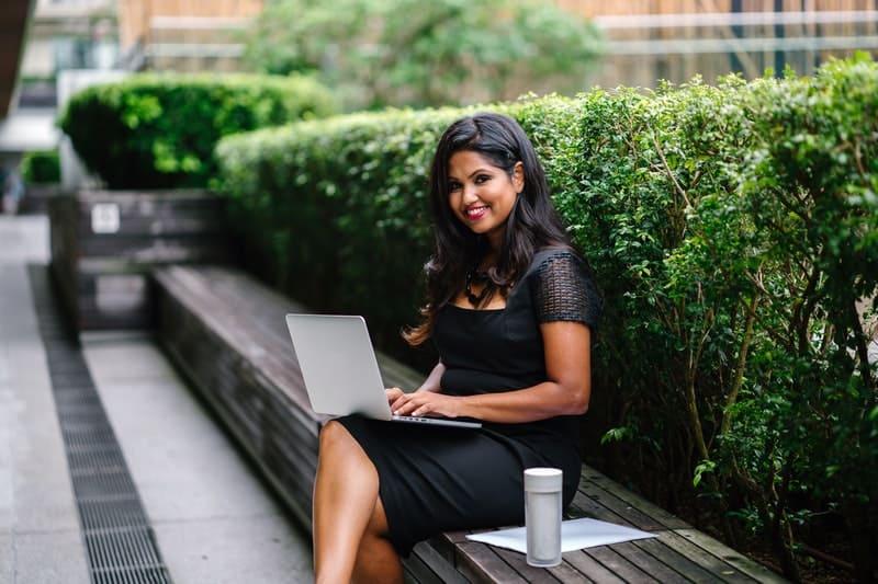 Frau im schwarzen Kleid auf Laptop