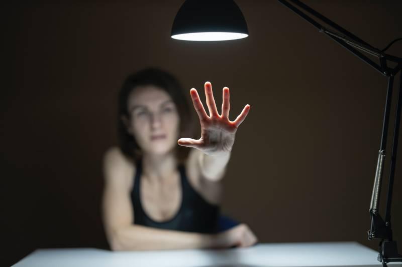 Frau im schwarzen Trägershirt, die ihre Hände hebt