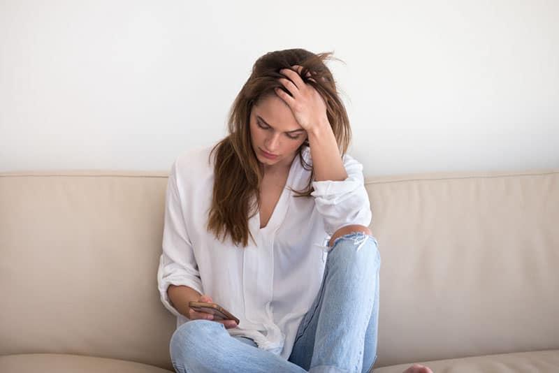 Frau im weißen Hemd, das Telefon betrachtet