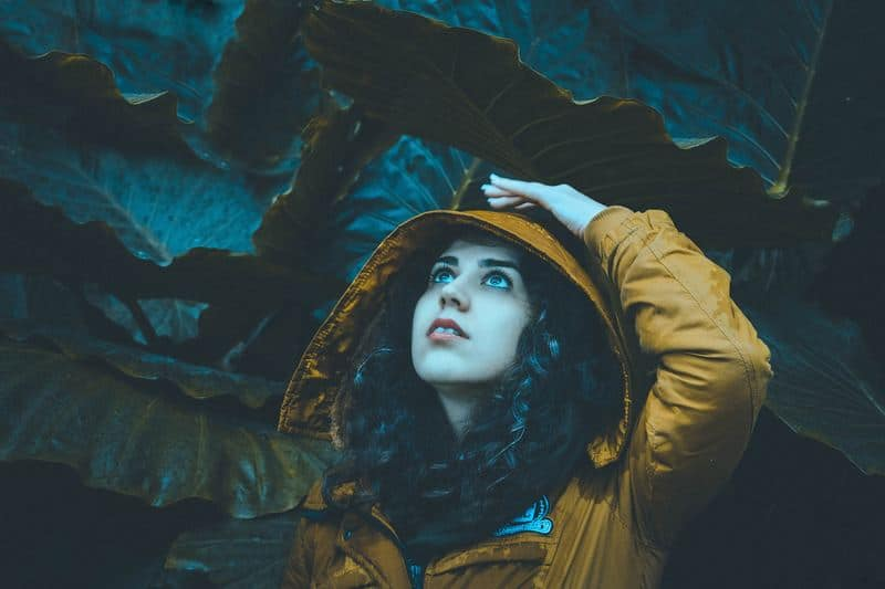 Frau in Regenmantel unter den Blättern