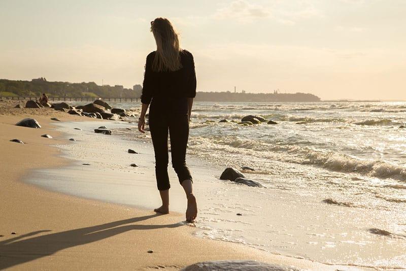 Frau in Schwarz geht auf dem Sand