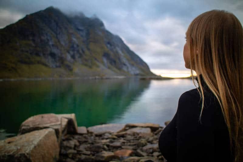 Frau in der schwarzen Jacke sitzt auf Felsen nahe See während des Tages