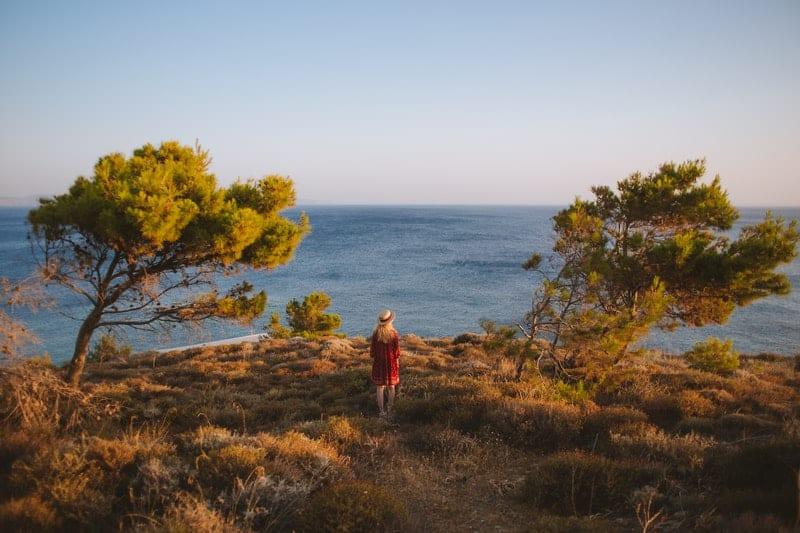 Frau in roten Kleid schaut auf das Meer