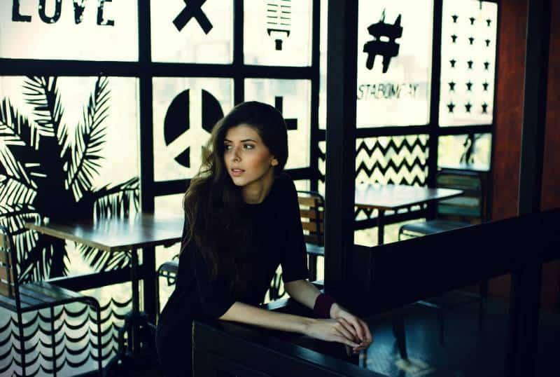Frau in schwarzem Viertelärmeloberteil, das sich auf schwarzen Schreibtisch stützt