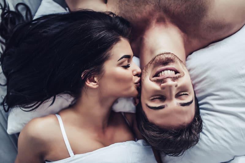 Frau küsst einen Mann im Bett