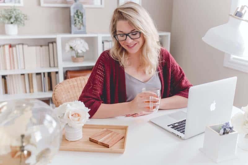 Frau lächelnd hält Glasbecher sitzend neben Tisch mit MacBook