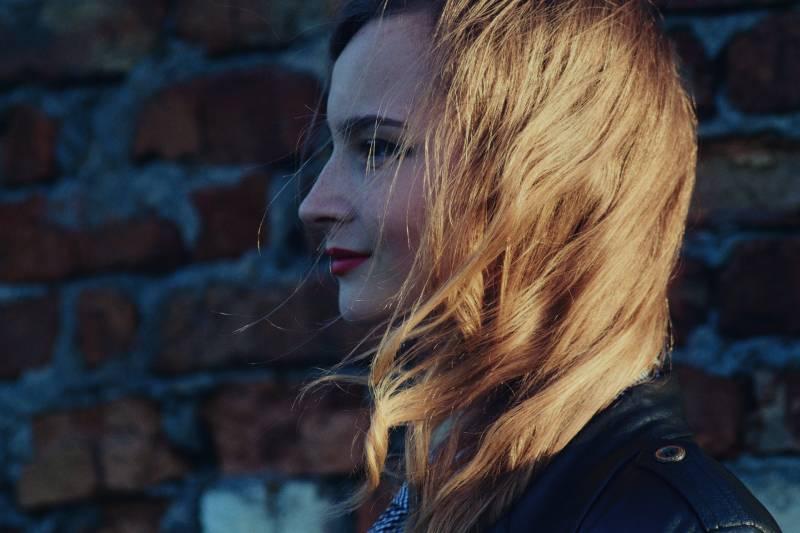 Frau lächelt neben Mauer