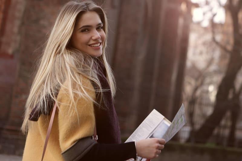 Frau lächelt und hält Papiere