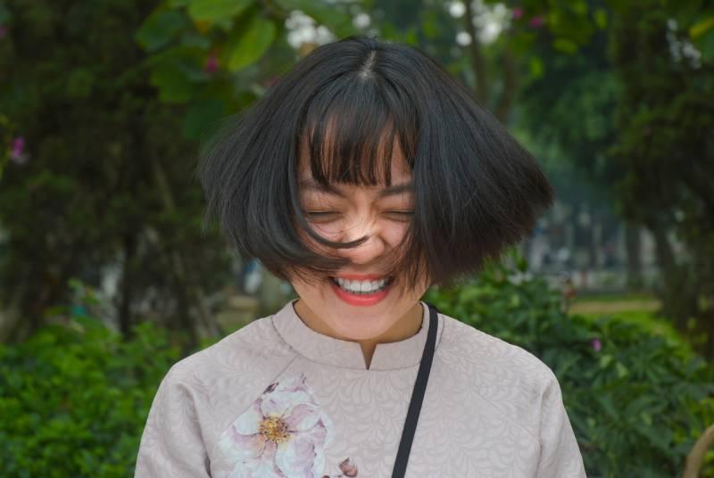 Frau lächelt und schließt die Augen, während sie ihre Haare dreht