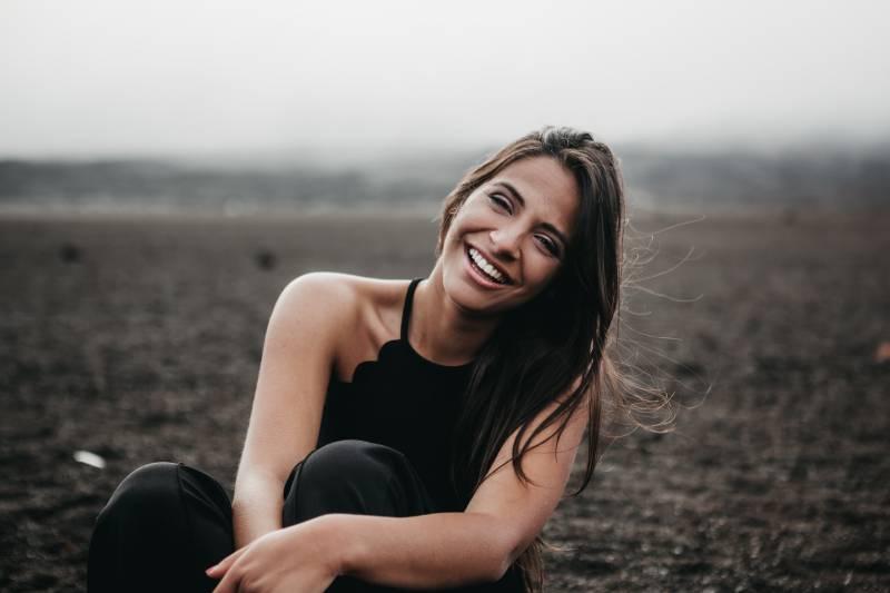 Frau lächelt, während sie auf dem Boden sitzt