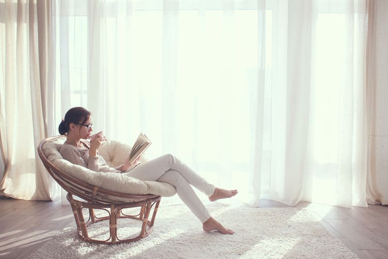 Frau liest ein Buch im Wohnzimmer