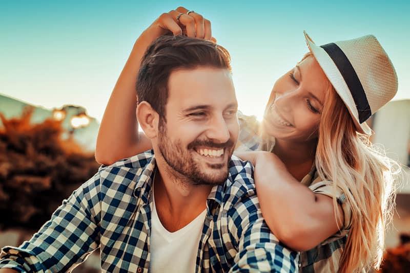 Frau mit Hut, der einen lächelnden Mann umarmt