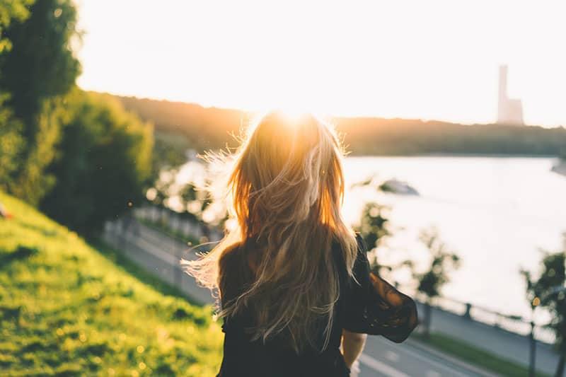 Frau mit Locken auf der Sonne stehend