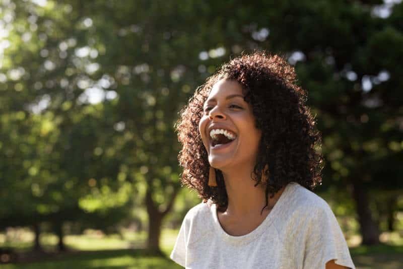 Frau mit dem lockigen Haar lachend, während sie draußen in einem Park steht
