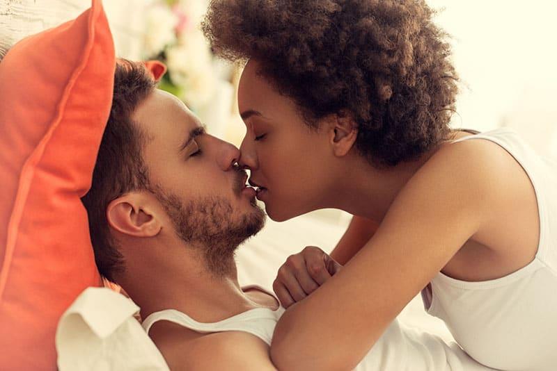 Frau mit lockigem Haar küsst einen Mann im Bett