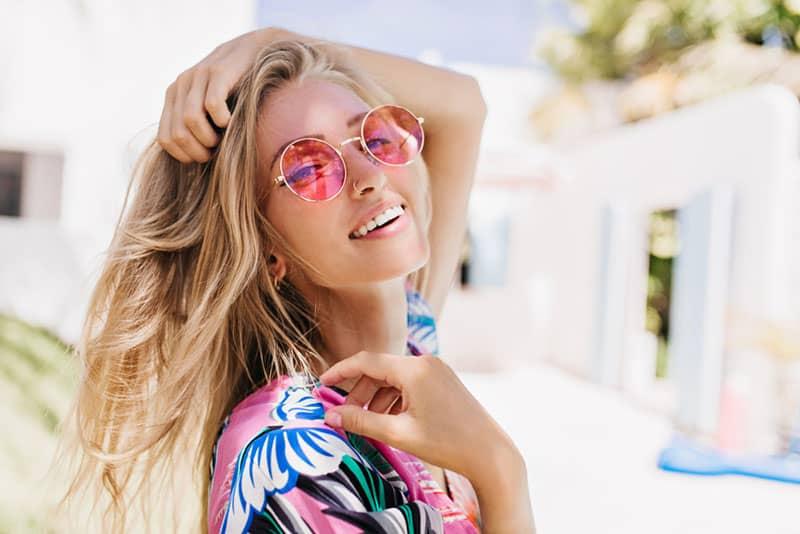 Frau mit rosa Brille lächelnd
