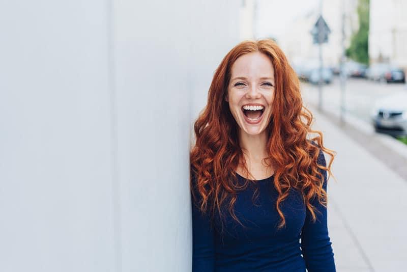 Frau mit roten Haaren lacht laut