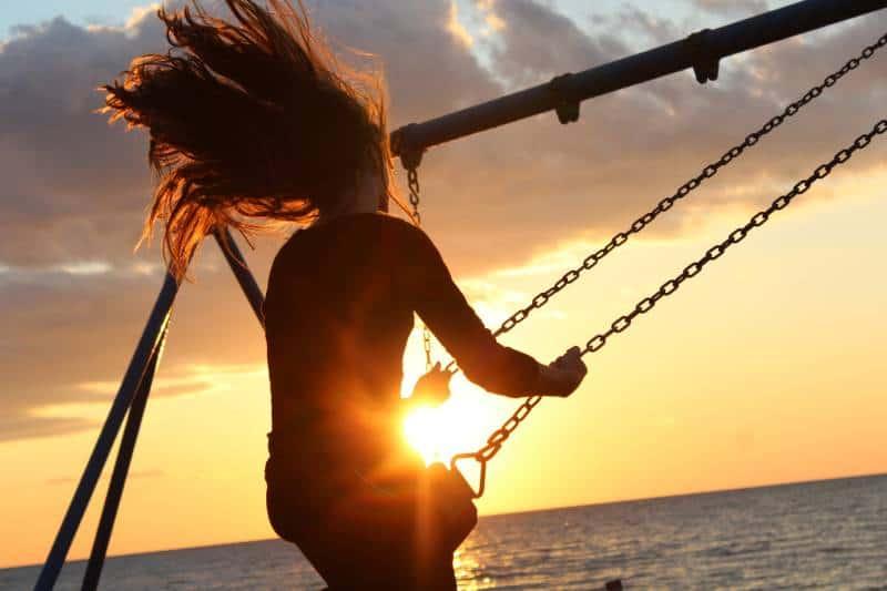 Frau reitet auf Schaukel während des Sonnenuntergangs