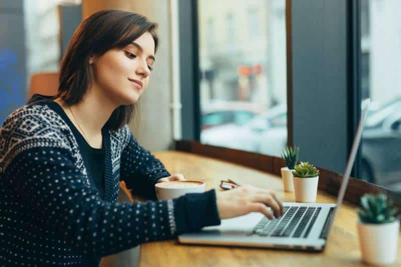 Frau schauen sich um und lächeln während der Arbeit im Cafe auf ihrem Laptop