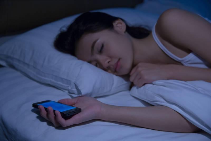 Frau schläft beim Telefonieren.