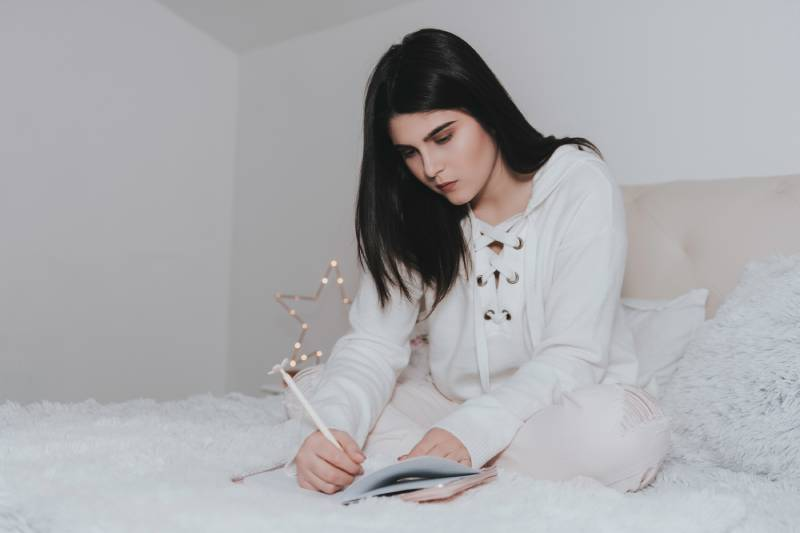 Frau schreibt einen Brief im Schlafzimmer