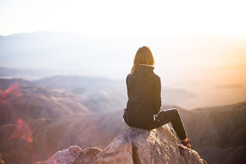 Frau sitzt allein auf dem Felsen