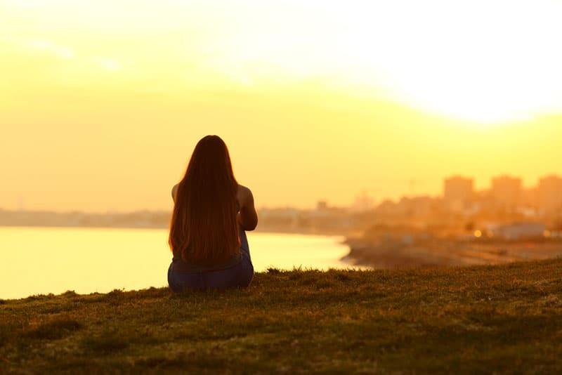 Frau sitzt alleine auf dem Hügel