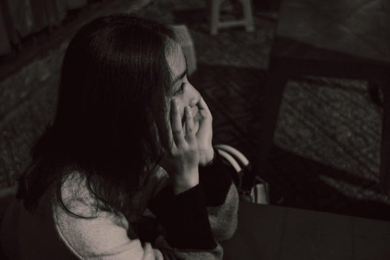 Frau sitzt alleine im Dunkeln
