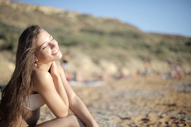 Frau sitzt am Strand im Bikini