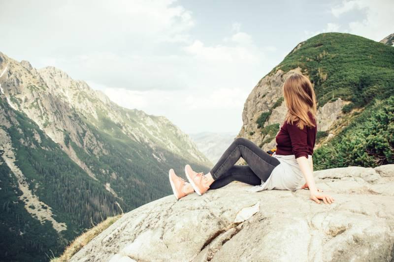 Frau sitzt auf Berggipfel