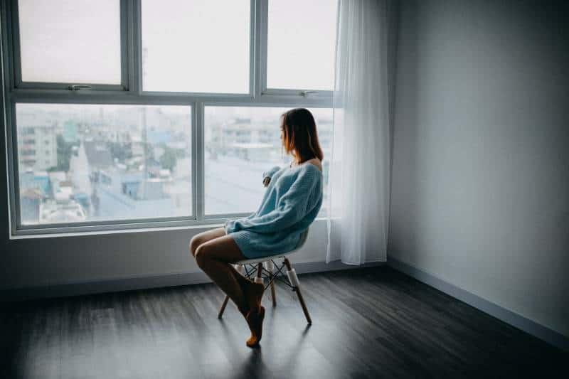 Frau sitzt auf braunem Stuhl vor dem Fenster