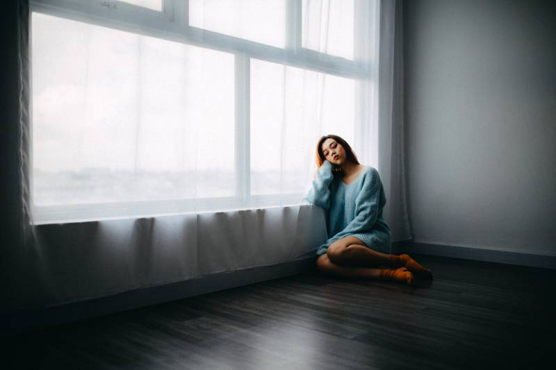 Frau sitzt auf dem Boden in der Nähe von Fenster