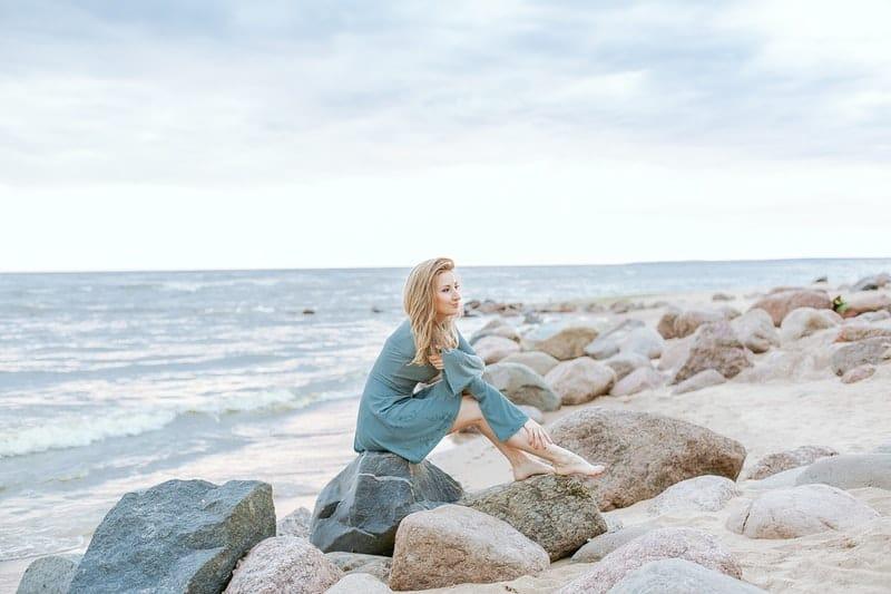 Frau sitzt auf grauen Stein in der Nähe des Meeres