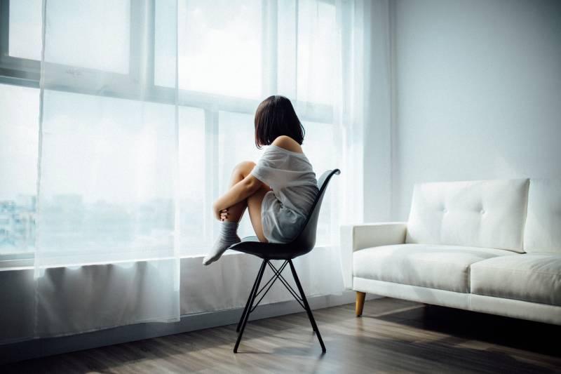 Frau sitzt auf schwarzem Stuhl zu Hause
