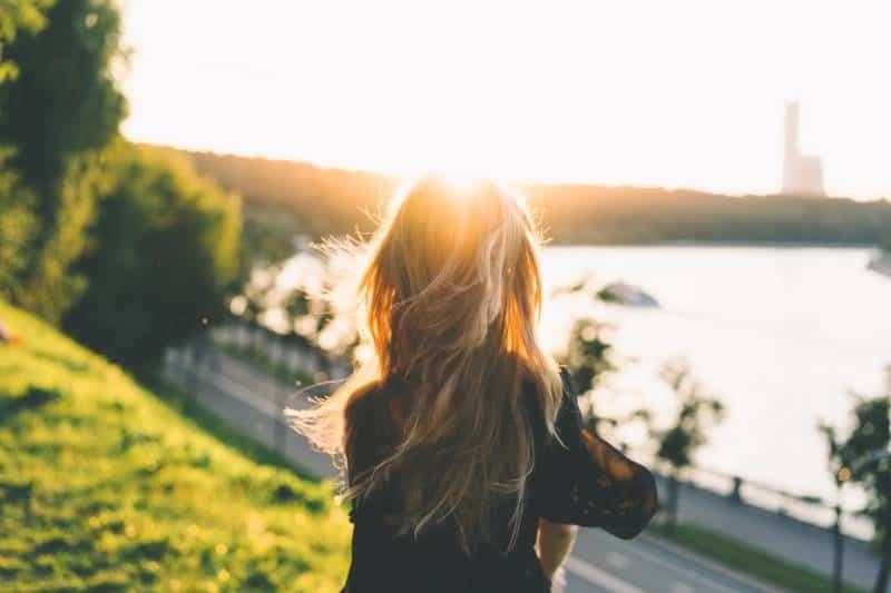 Frau sitzt beim Betrachten des Sonnenuntergangs
