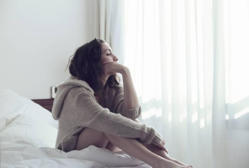 Frau sitzt im Schlafzimmer und schaut nach draußen