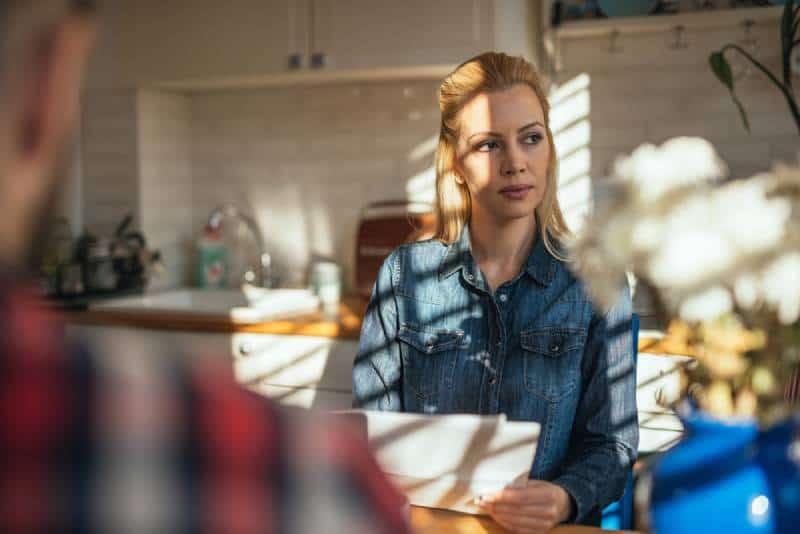 Frau sitzt in der Küche und denkt nach
