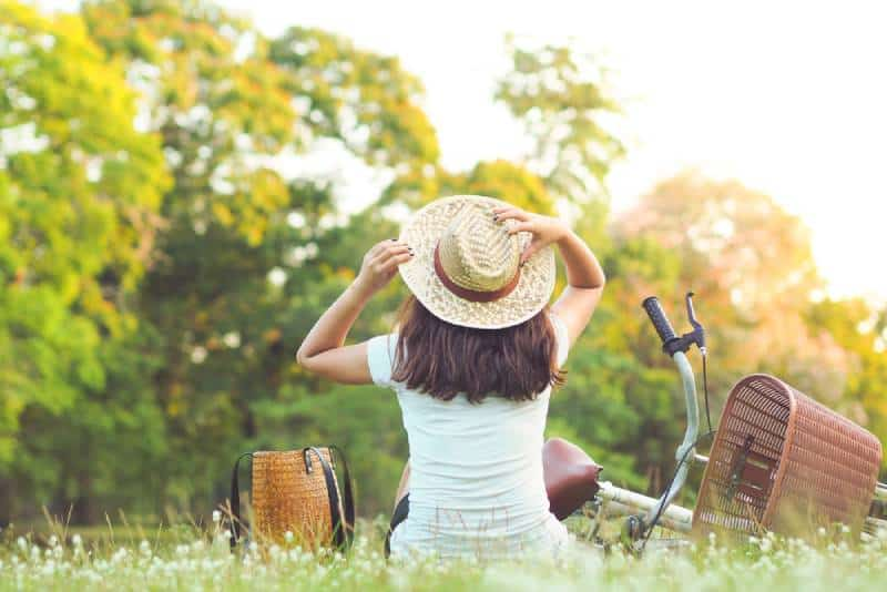 Frau sitzt in der Nähe ihres Fahrrads im Park
