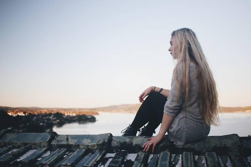 Frau sitzt und schaut See