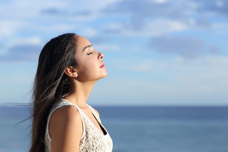 Frau tief am Meer atmen