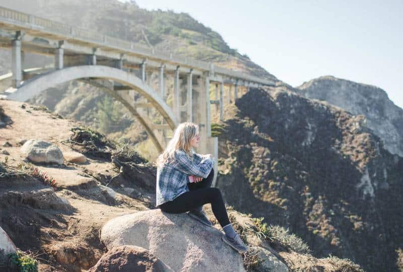 Frau trägt kariertes Hemd, das auf Felsen sitzt