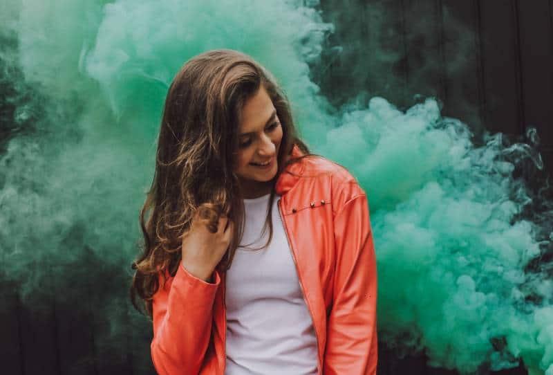 Frau trägt orange Lederjacke von grünem Rauch umgeben
