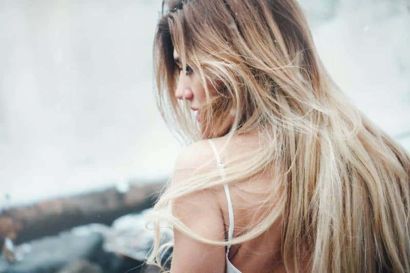 Frau trägt weißes Spaghettiträgeroberteil mit blonden Haaren