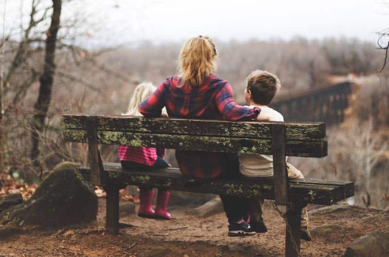 Frau zwischen zwei Kindern, die tagsüber auf brauner Holzbank sitzen