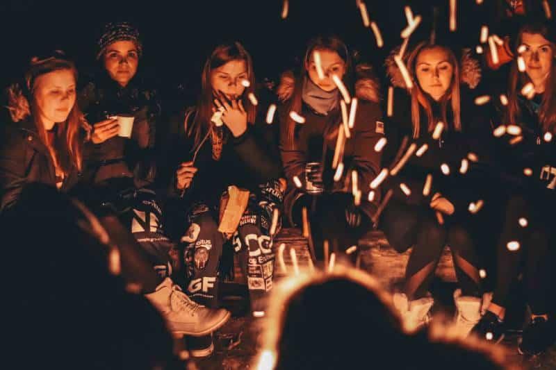 Frauen in der Nähe von Lagerfeuer in der Nacht