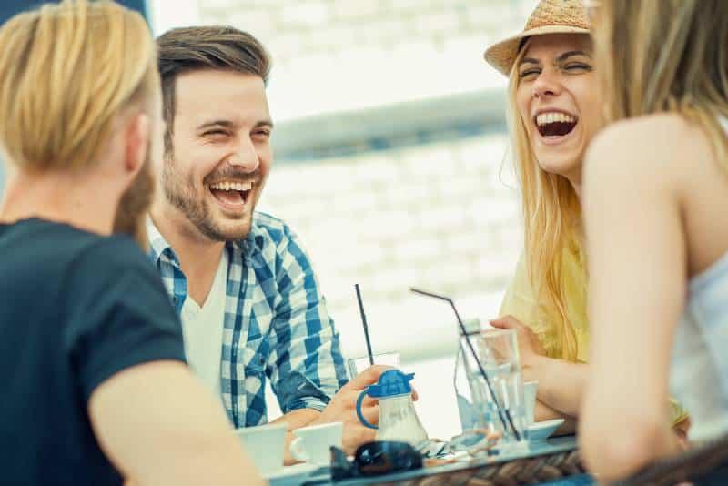 Freunde lächeln und sitzen in einem Café, trinken Kaffee und genießen zusammen