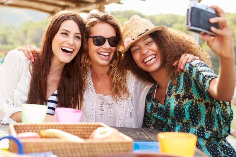 Freundinnen, die Selfie während des Mittagessens im Freien nehmen