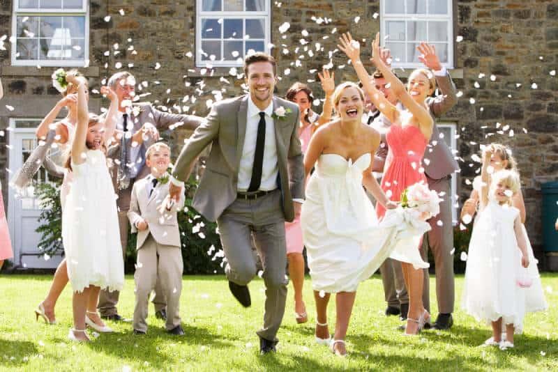 Gäste werfen Konfetti über Braut und Bräutigam
