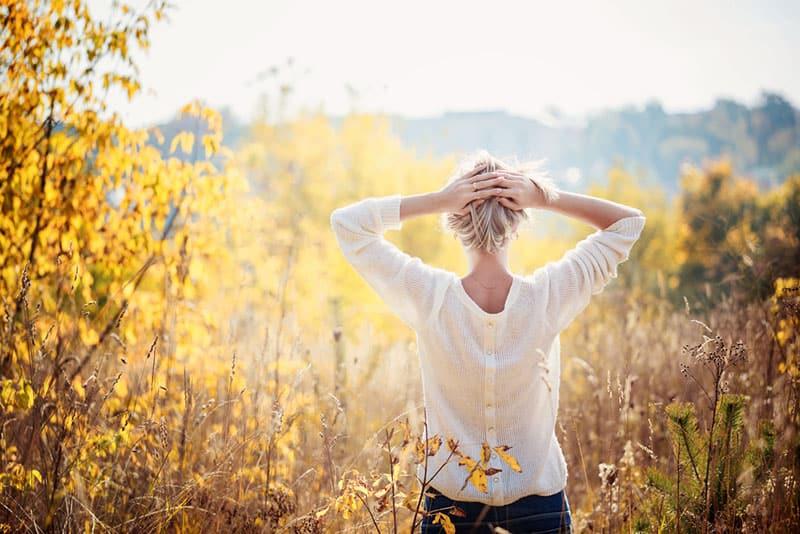 achtsame Frau mit gezogenem Haar, das in der Natur steht